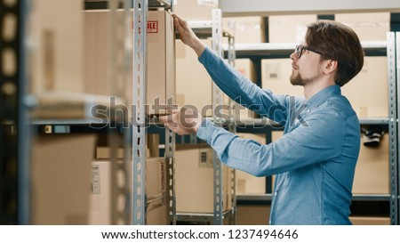 Warehouse Worker Puts Cardboard Box on a Shelf. In the Background Rows of Shelves Full of Cardboard Boxes and Parcels Filled with Products Ready for Shipment.