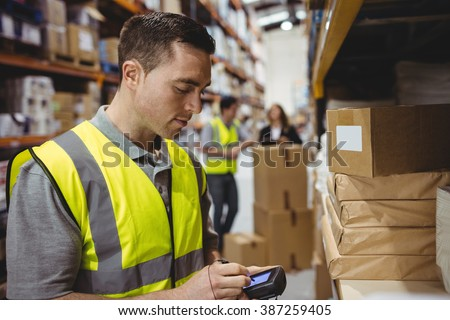 Warehouse worker scanning box in warehouse