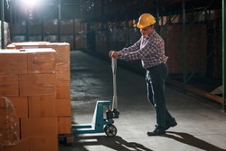Warehouse worker selecting packages at the storehouse.Night shift.