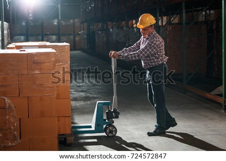 Warehouse worker selecting packages at the storehouse.Night shift. #724572847