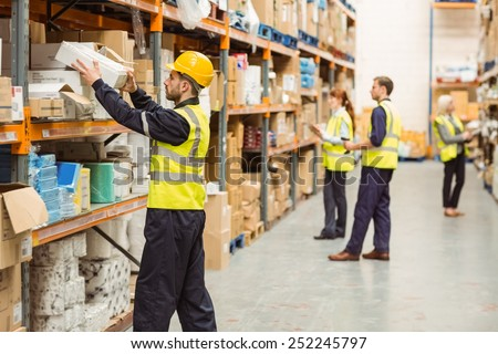 Warehouse worker taking package in the shelf in a large warehouse in a large warehouse #252245797