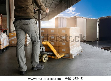Warehouse Worker Unloading Package Boxes into Cargo Container Truck.Trailer Truck Parked Loading at Dock Warehouse. Delivery Service. Shipping Warehouse Logistics. Freight Truck Transportation.