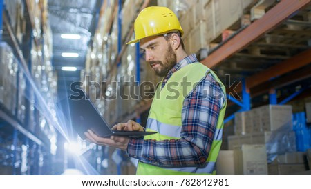 Warehouse Worker Uses Laptop. He's Standing in the Middle of  a Big Distribution Center with Big Storage Racks and Pallets on Them. #782842981