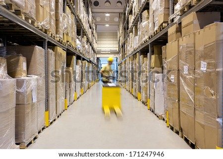 Warehouse worker with a yellow hand pallet truck