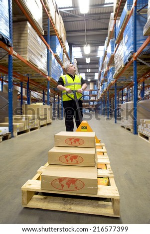 Warehouse worker with boxes on pallet truck looking up at shelves