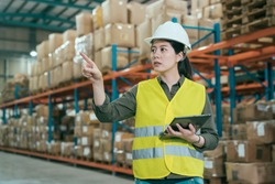 warehouse worker woman in safety vests holding digital tablet and pointing up with finger. young girl staff wearing hard hat working in stockroom. elegant lady employee taking inventory in storehouse