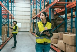 Warehouse worker woman wearing headset holding clipboard in large warehouse. blurred view colleague in safety vest standing stock taking. lady staff answering phone call and talking by microphone