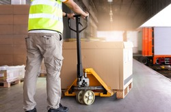 Warehouse worker working with hand pallet truck loading heavy boxes on pallet into cargo container. Shipment, Delivery sevice, Cargo freight truck. Warehousing and Logistics.