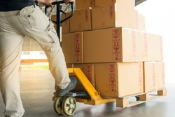 warehouse worker working with hand pallet truck, stack cardboard boxes on wooden pallet,  cargo shipment and transportation.