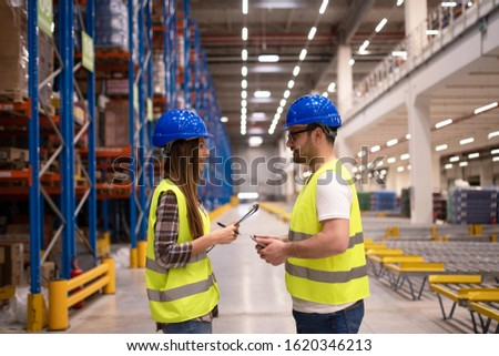 Warehouse workers discussing about work.