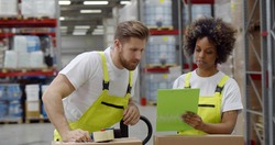 Warehouse workers sealing cardboard boxes for shipping in large warehouse. Diverse employees packing goods in industrial storehouse for shipping