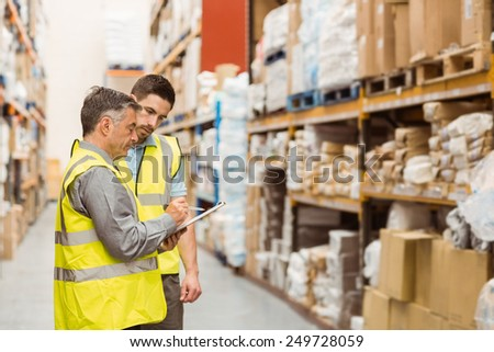 Warehouse workers talking together at work in a large warehouse #249728059