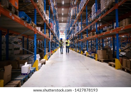 Warehouse workers walking in large factory storage area. Employees checking logistics and distribution of goods to the market.