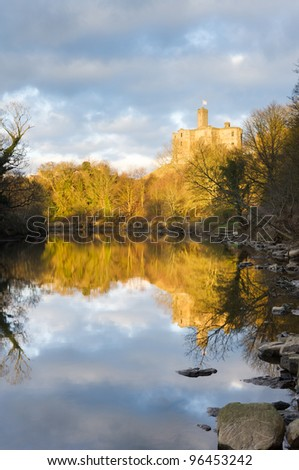 Warkworth Castle reflected / Warkworth castle lit by evening sunlight reflected in the river Coquet - stock photo