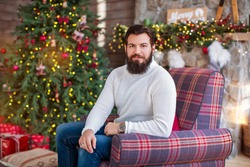 Warm and cozy christmas atmosphere at home.  Man bearded in sweater relax sit armchair near christmas tree. Feel like home.