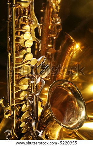 Warm and golden lite saxophone against reflective background with copy space