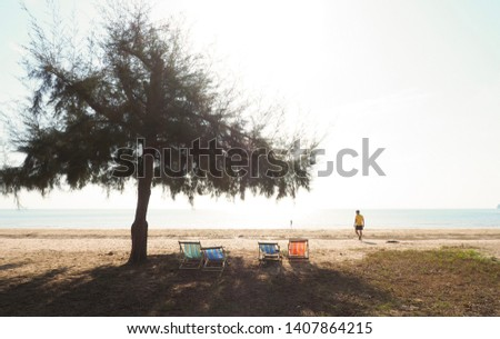 Warm and vintage tone of a lonely man walking on the silent beach on holidays in the morning with sunlight, lone tree and wooden beach chairs Weekend getaway, nature, new day and inspirational concept