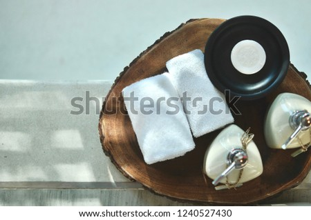 Warm atmosphere in spa resort, Close up of spa essentials and towels on wooden tray in bathroom, essential oil. Spa products set conception. #1240527430