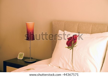 Warm bedroom with wardrobe and large bed with pillows and roses sheets. - stock photo