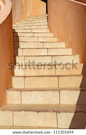 Warm beige stones wind upwards towards the top of a staircase in Belize City, central America