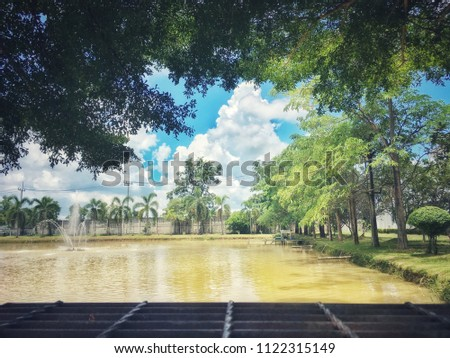 Warm blue sky, lush greenery and lush green lawns and large ponds. #1122315149