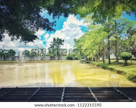 Warm blue sky, lush greenery and lush green lawns and large ponds. #1122315590