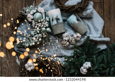 Warm blue wool sweater, hand made candles, cotton, spruce leaves, christmas themed wooden wreaths and fireflies on the wooden floor background, top view, flat lay