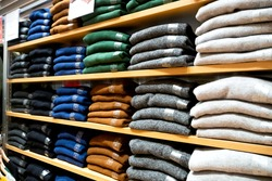 Warm clothing neatly folded on a shelf. A row of colorful jumpers, cardigans, sweatshirts, sweaters, hoodies in the showroom or store