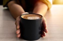 Warm coffee in a black mug with woman hand.