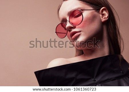 Warm colored fashion portrait of beautiful young woman in round red sunglasses and grey latex jacket posing in studio - Shutterstock ID 1061360723