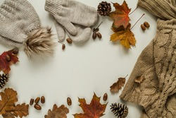 Warm, cosy knitted winter sweater, gloves and hat with pom pom. Fall flat lay composition with acorns, cones and autumn leaves. Copy space on white background.