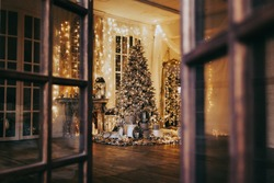 warm cozy evening in Christmas room interior design,Xmas tree decorated lights gifts, deer,candles, lanterns, garland lighting indoors fireplace.holiday.magic New year.open door to fairy tale