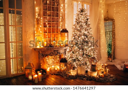warm cozy evening in luxury Christmas room interior design, Xmas tree decorated by lights presents gifts toys, candles, lanterns, garland lighting fireplace.holiday living room. New year holidays #1476641297