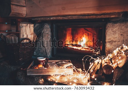 Warm cozy fireplace with real wood burning in it. Magical atmosphere. Cup of hot drink and book ready for evening relax. Cozy winter concept. Christmas and travel background with space for your text. #763093432