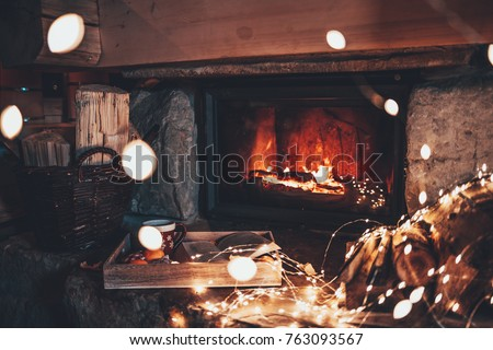 Warm cozy fireplace with real wood burning in it. Magical atmosphere. Cup of hot drink and book ready for evening relax. Cozy winter concept. Christmas and travel background with space for your text. #763093567