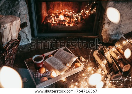 Warm cozy fireplace with real wood burning in it. Magical atmosphere. Cup of hot drink and book ready for evening relax. Cozy winter concept. Christmas and travel background with space for your text. #764716567