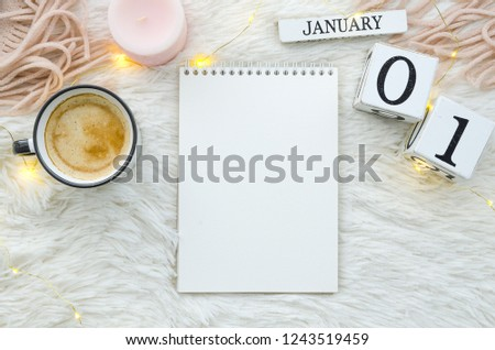 Warm cozy home start new year 1 january on perpetual calendar. Notebook mockup cup of coffee, candle and lights. Flat lay top view #1243519459