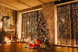 warm cozy magic evening in luxury old Christmas room fairy tale interior design,pahoramic windows,fire place  Xmas tree decorated by lights,gifts, candles, lanterns, garland lighting.New year holidays