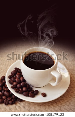 Warm cup of coffee with a coffee beans on background