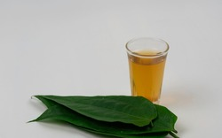 Warm drinks in a glass cup made from Thunbergia laurifolia leaves, isolated on white background. Herbal drink Thailand.