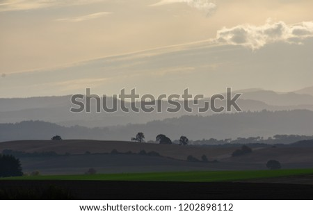 Warm dusty tones in a hazy scene of hills layered under a soft sky, silhouette of trees and hills layered behind farm fields.