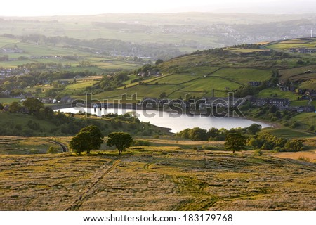 warm evening sunlight warms the landscape around a yorkshire reservoir in the heart of bronte country.