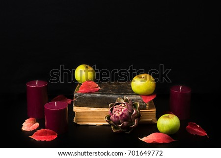 Warm fall composition on black background. Old books, candles, green apples, artishok and red autumn leaves making cozy romantic atmosphere. Copy space #701649772