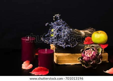 Warm fall composition on black background. Old books, candles, green apples, dry lavender, artishok and red autumn leaves making cozy romantic atmosphere. Copy space #701013196