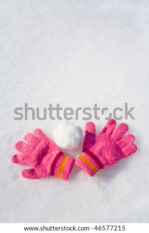 Warm female pink gloves and snowball on fresh snow.