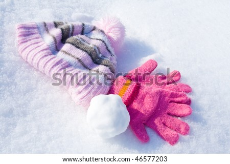 Warm female pink gloves, cap and snowball on fresh snow.