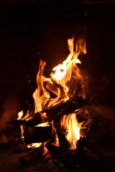 Warm fire and sparks in a fire-place from conflagrant wooden logs