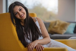 Warm friendly sincere portrait of a likable and genuine mixed ethnicity Indian woman at home relaxing on the sofa