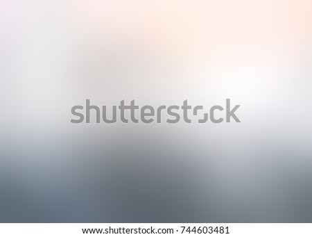 Warm glow on cold grey backdrop. Silver empty background. Pearl defocused background. Metallic abstract texture. Grey glare blurred texture.