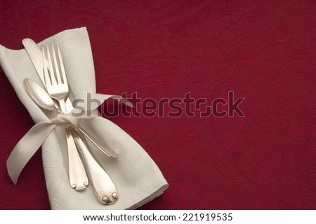 Warm Holiday or Romantic Place Setting with Sterling Silverware in White Napkin and Ribbon on Red Background with Copy space or Room for Your Text or Words.  Horizontal above view.